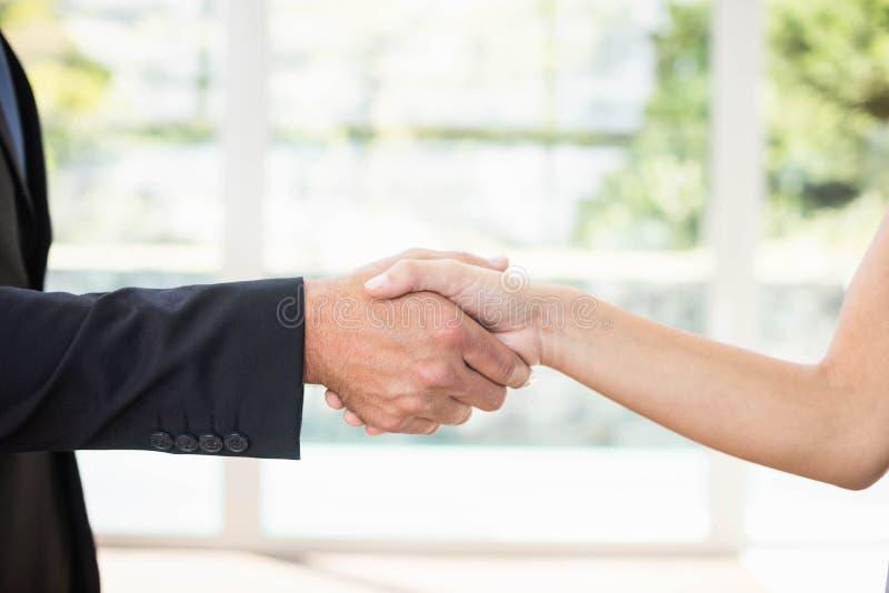 Agent immobilier serrant la main au client images stock
