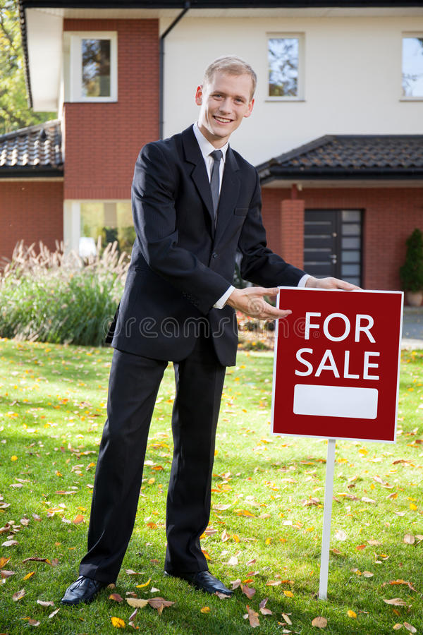 Agent immobilier tenant le signe dehors photographie stock