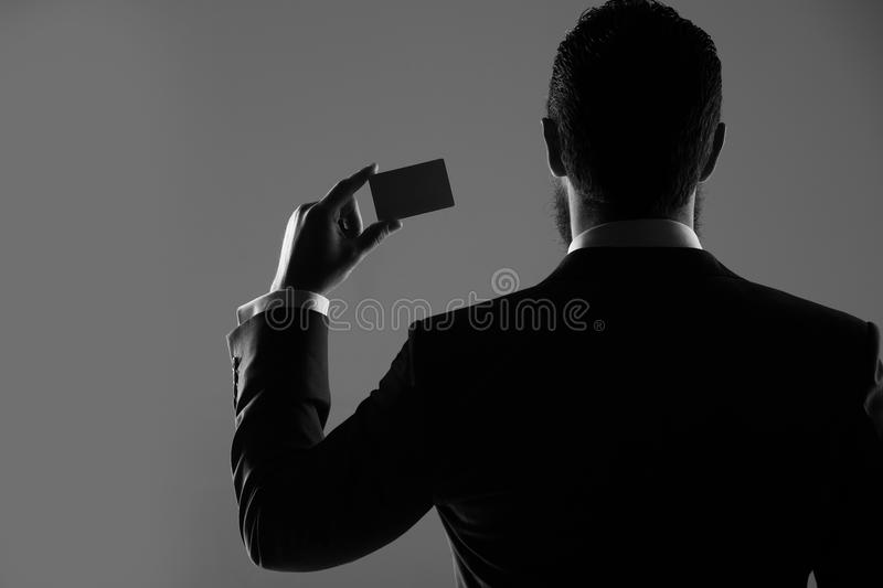 Agent of insurance, man with business, credit card, business ethics. Agent of insurance or man with business or credit card in formal outfit in shadow on grey stock photography