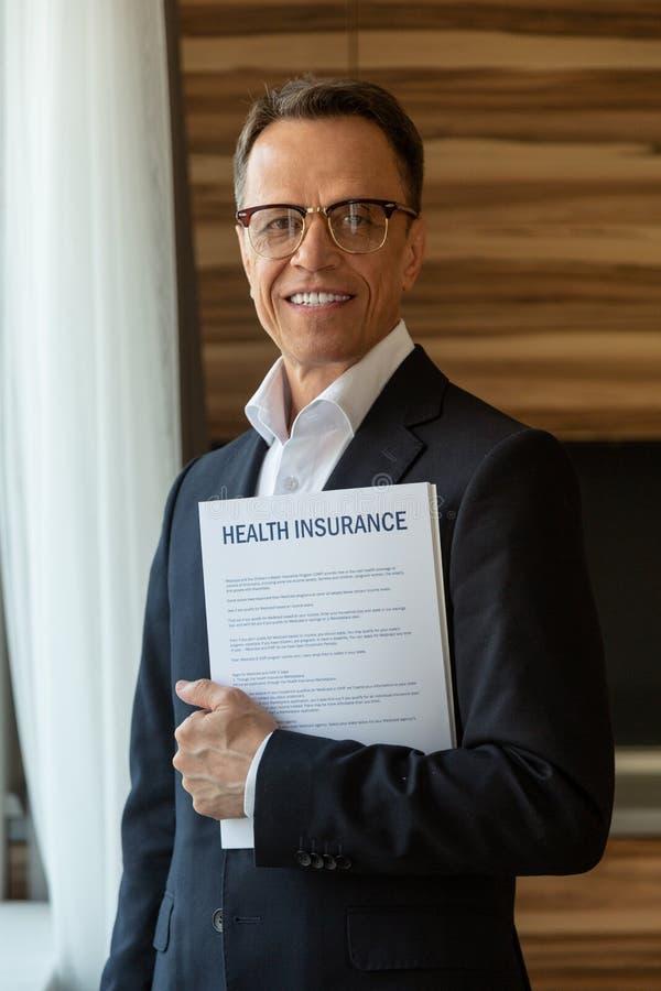 agent mûr aux cheveux foncés d'assurance médicale maladie dans le sourire de lunettes photos libres de droits