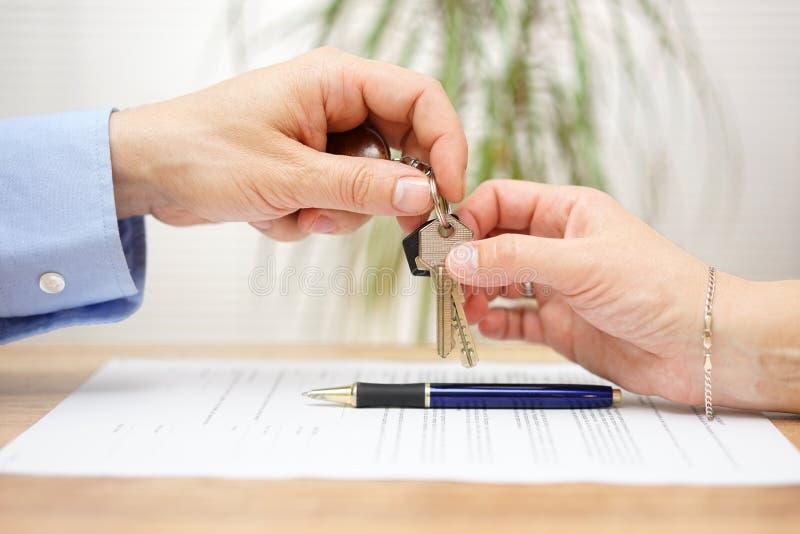 Agent nieruchomości daje domowym kluczom jego klient po podpisywać c obraz royalty free