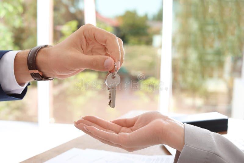 Agent nieruchomości daje kluczowi kobieta obraz stock