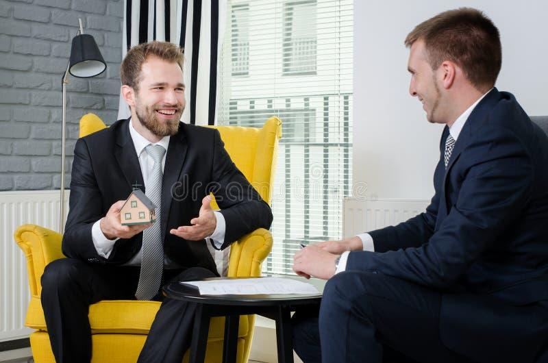 Agent nieruchomości dyskutuje z projektami i domu modelem obraz royalty free