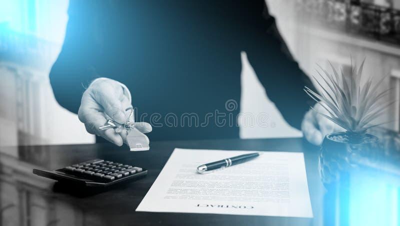 agent nieruchomości, który pokazuje klucze domu; ekspozycja wielokrotna obraz stock