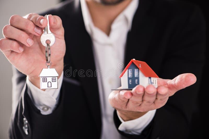 Agent nieruchomości trzyma domowej klucza i domu wzorcowej un palma zdjęcie stock
