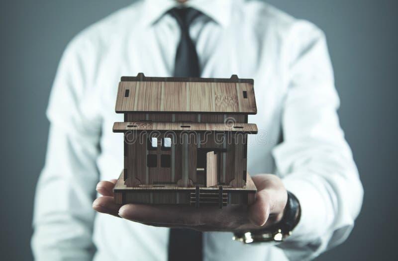Agent nieruchomości trzyma drewnianego dom koncepcja real nieruchomości obrazy stock