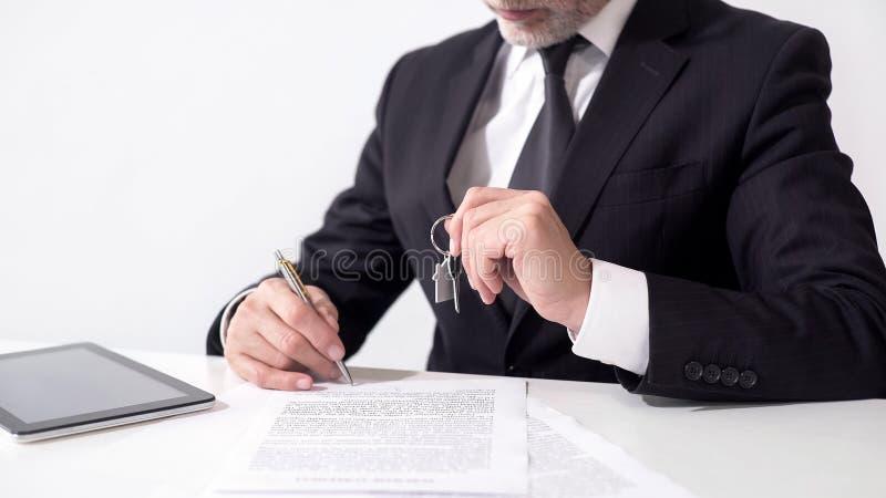 Agent nieruchomości trzyma out domowych klucze klient i podpisuje hipotecznych papiery fotografia royalty free