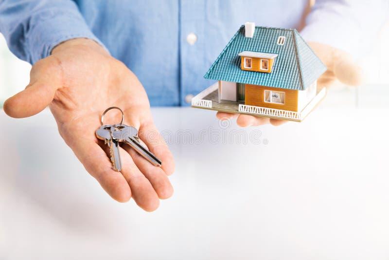 Agent nieruchomości z domów kluczami w rękach i modelem obraz stock