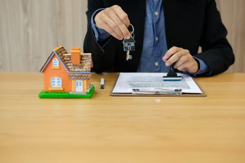 agent nieruchomości z domu klucza cechowaniem zatwierdzał na hipotecznej pożyczki kontraktacyjnej zgody dokumencie obrazy stock