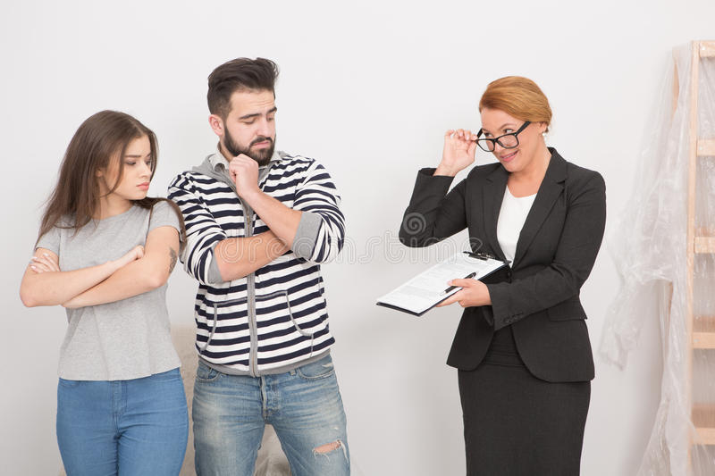Agent proposing to sign rent cotntact to a hesitating couple. Young men and women arguing with estate gagent royalty free stock photography