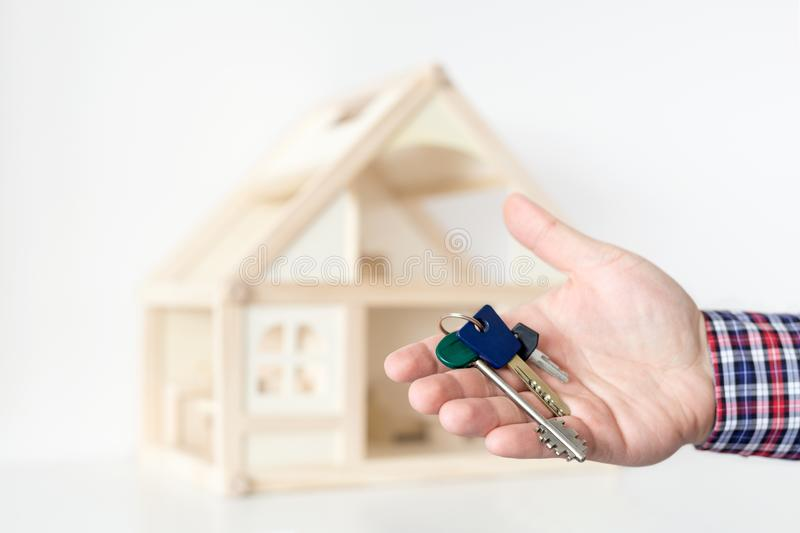 Agent`s hand hold keys against house model on background. Realtor sale offer. Real estate investment proposition. Buying new ho. Use concept royalty free stock photo