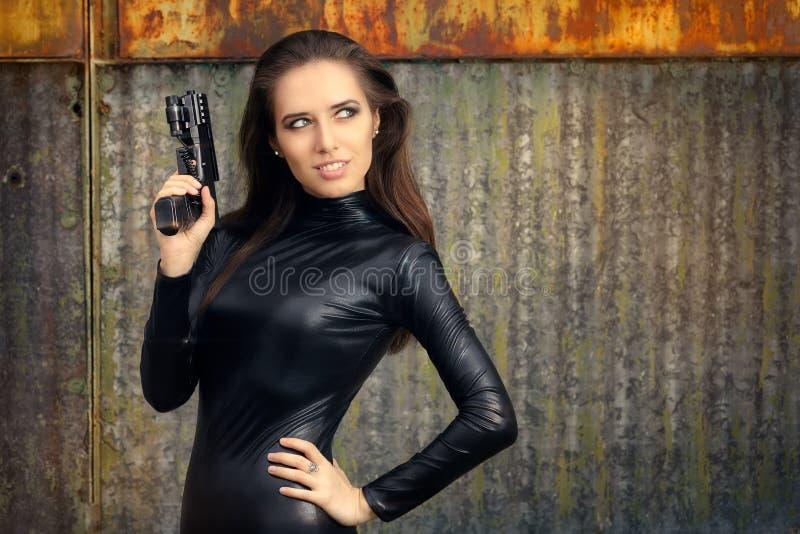 Agent Woman d'espion dans le costume en cuir noir tenant l'arme à feu photos stock
