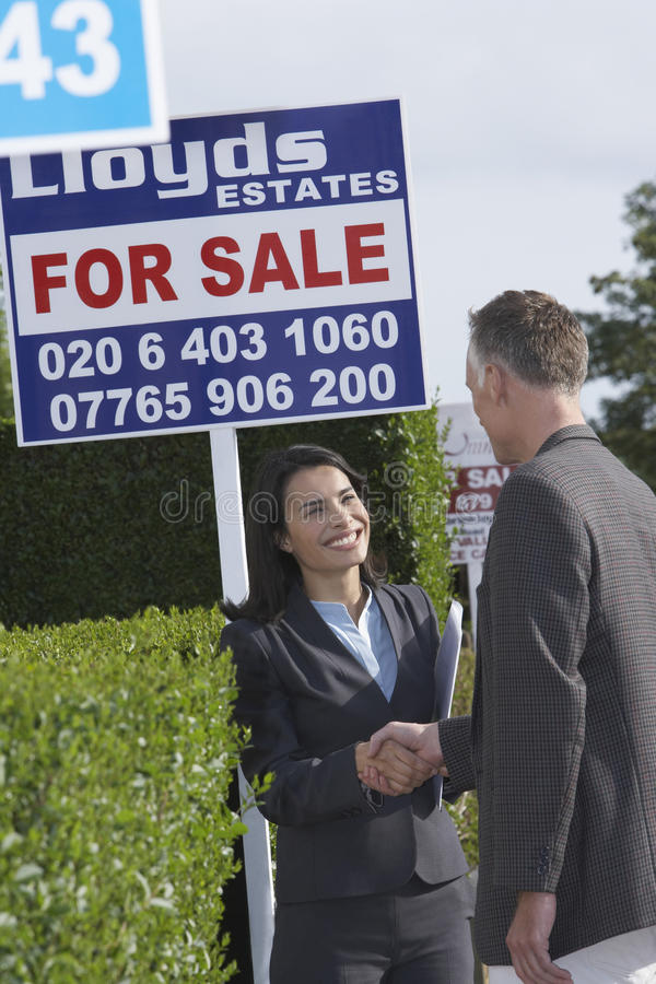 Agenta Nieruchomości I mężczyzna chwiania ręki sprzedaż znakami obrazy royalty free