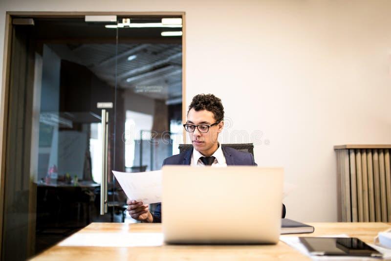 Agente acertado de sexo masculino que trabaja en netbook portátil Economista que usa el cuaderno imágenes de archivo libres de regalías
