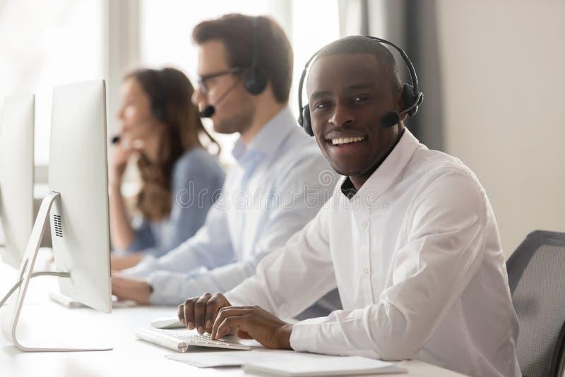 Agente africano feliz del centro de atención telefónica en las auriculares que presentan en el lugar de trabajo fotos de archivo