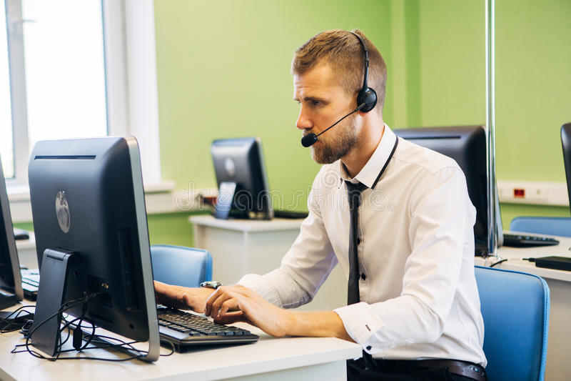 Agente allegro che lavora in una call center con la sua cuffia avricolare immagini stock libere da diritti