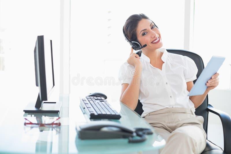 Agente allegro di call-center facendo uso della sua compressa digitale su una chiamata fotografia stock