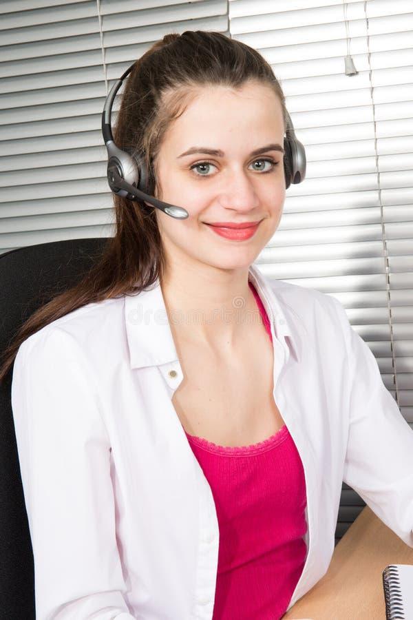 Agente amichevole della donna dell'operatore con le cuffie avricolari che funzionano in un call-center immagine stock libera da diritti