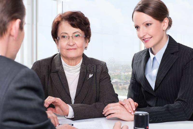 Agente con la donna senior e sua figlia fotografia stock libera da diritti