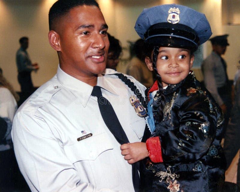 Agente da polícia com sua filha em sua graduação da polícia fotografia de stock