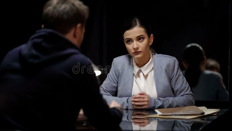 Agente da polícia da mulher que interroga o suspeito masculino na sala escura, desconfiança, igualdade fotografia de stock