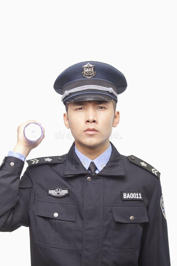 Agente da polícia novo sério Shining Flashlight na câmera, tiro do estúdio fotos de stock