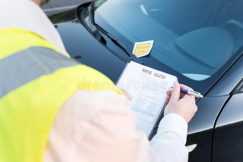 Agente da polícia que dá uma multa para a violação de estacionamento imagem de stock royalty free
