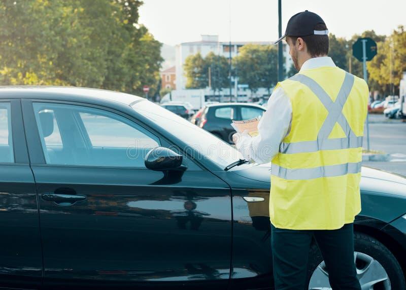 Agente da polícia que dá uma multa para a violação de estacionamento foto de stock