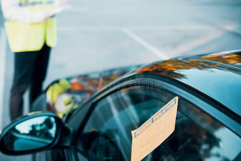 Agente da polícia que dá uma multa para a violação de estacionamento imagem de stock
