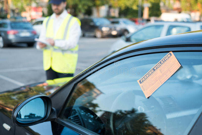 Agente da polícia que dá uma multa para a violação de estacionamento imagens de stock royalty free