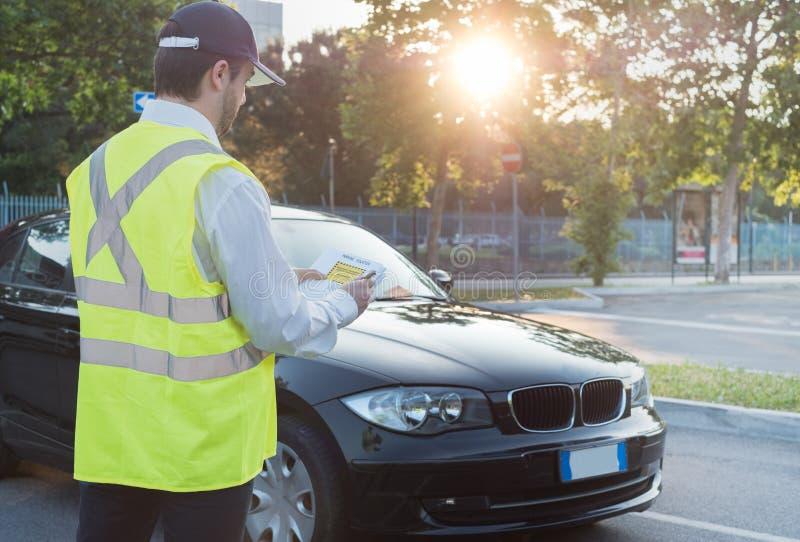 Agente da polícia que dá uma multa para a violação de estacionamento fotos de stock royalty free