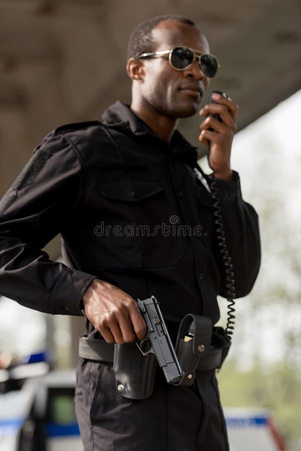 agente da polícia que fala pelo grupo de rádio do Walkietalkie imagens de stock