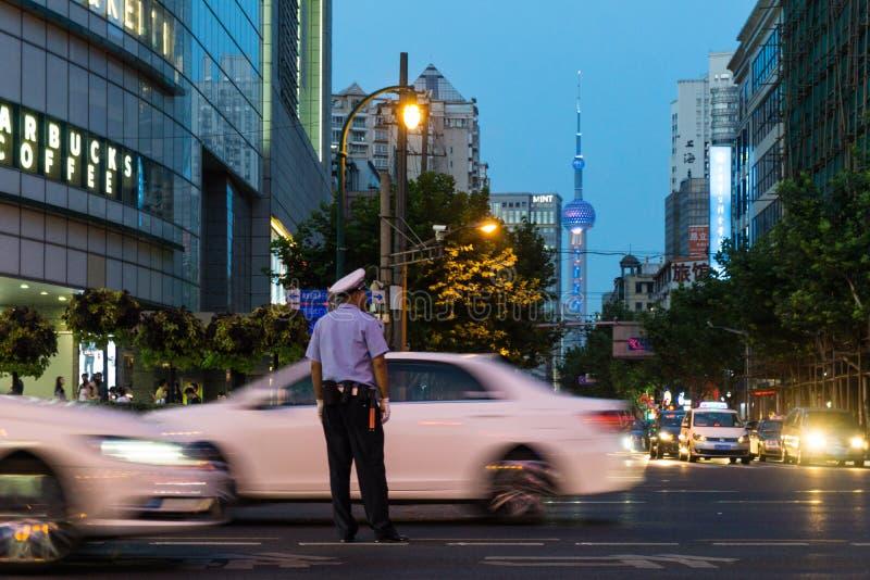 Agente da polícia que tenta controlar a loucura do tráfego em Shanghai Os carros estão apressando-se por e na distância está o di imagens de stock