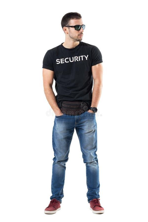 Agente da polícia secreto em vestido à paisano com mãos em uns bolsos que olham afastado imagens de stock