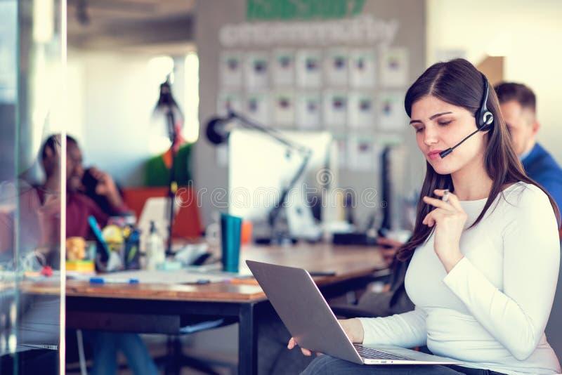 Agente de atendimento ao cliente em um escritório de inicialização com laptop fotografia de stock