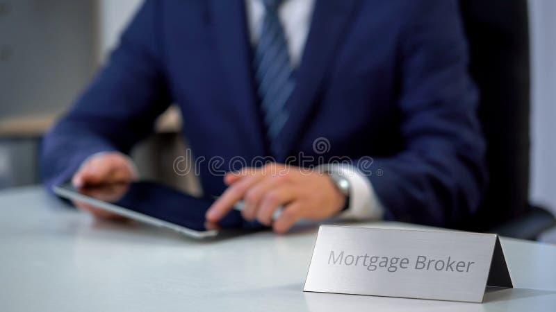 Agente de hipoteca profesional usando la PC de la tableta, buscando las ofertas de préstamo para el cliente foto de archivo