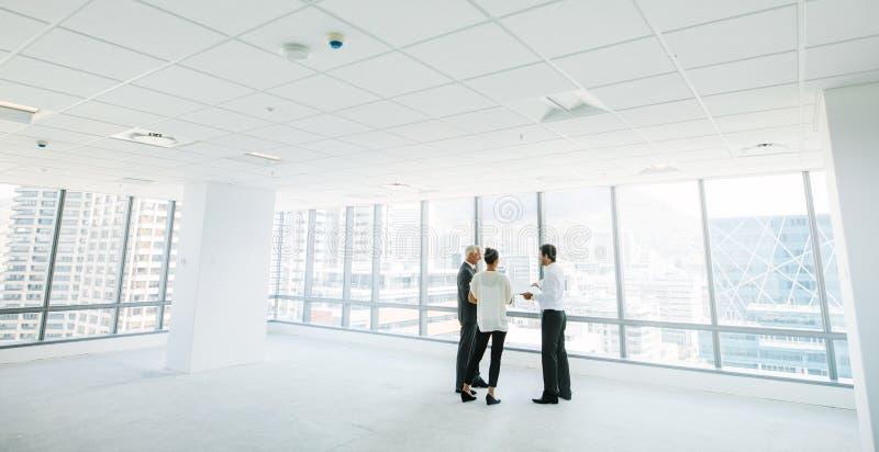 Agente de la propiedad inmobiliaria con los clientes dentro de un espacio de oficina vacío fotos de archivo