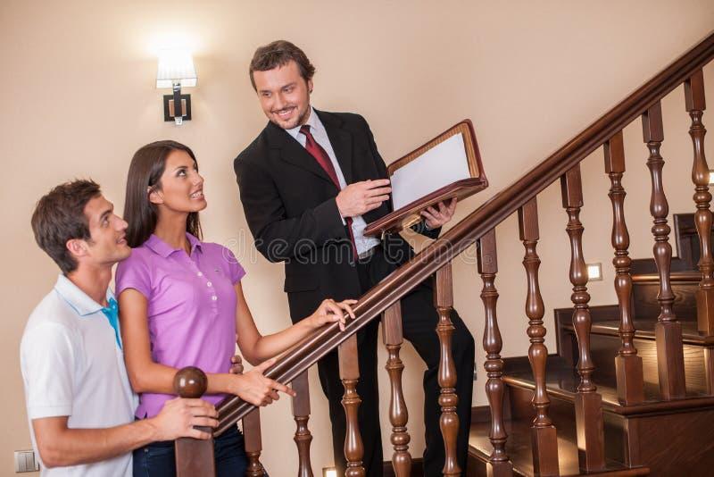 Agente de la propiedad inmobiliaria con los pares jovenes en escalera fotos de archivo libres de regalías