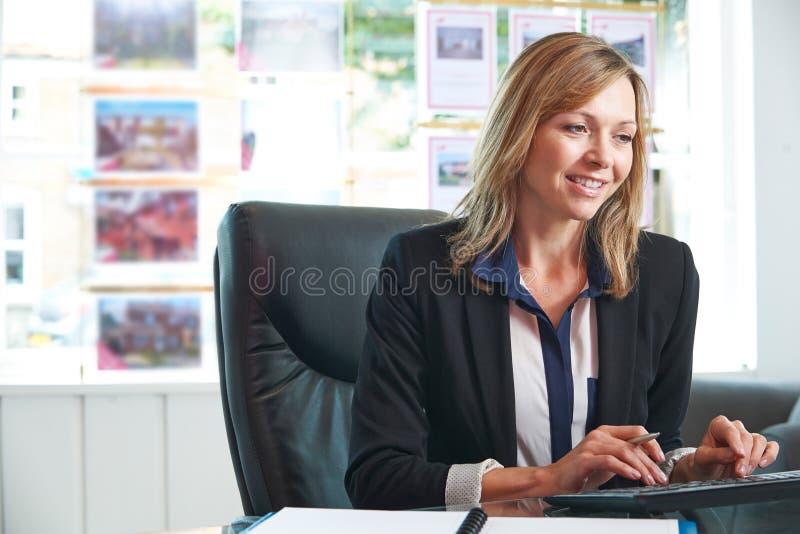 Agente de la propiedad inmobiliaria de sexo femenino Working At Computer en oficina fotos de archivo
