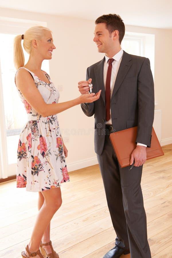 Agente de la propiedad inmobiliaria Handing Over Keys al comprador femenino de la casa imágenes de archivo libres de regalías