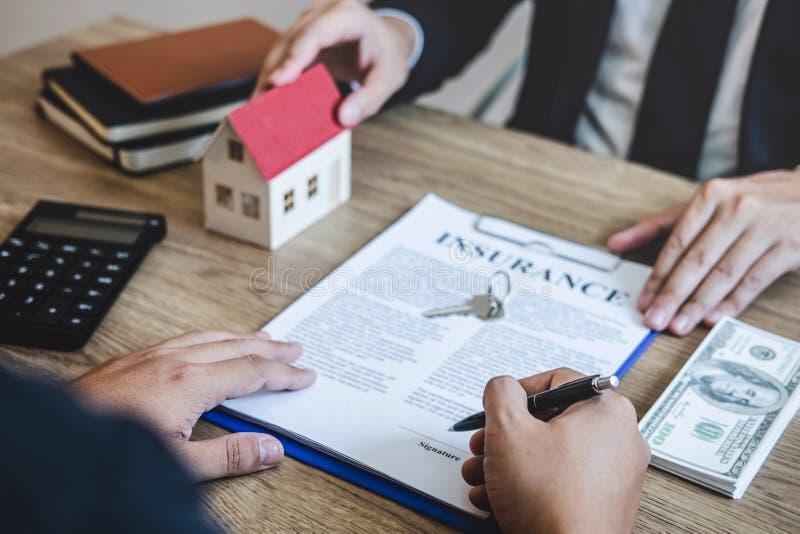Agente de la propiedad inmobiliaria que da la casa y llaves al cliente después de firmar las propiedades inmobiliarias del contra fotografía de archivo libre de regalías