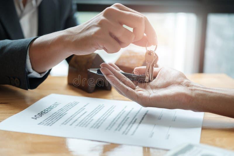 Agente de la propiedad inmobiliaria que da llaves de la casa para servir y para firmar el acuerdo en offi fotografía de archivo