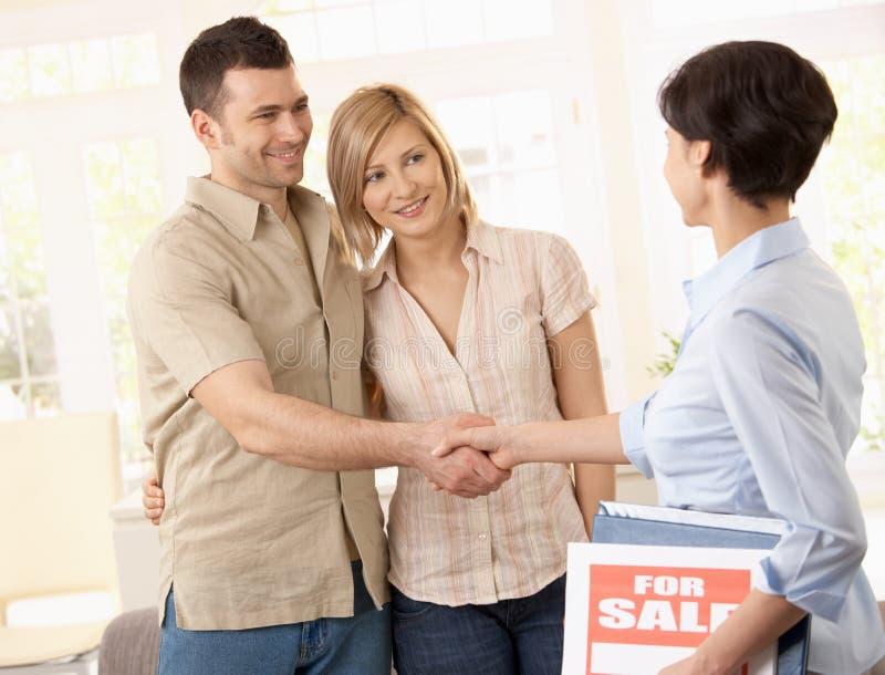 Agente de la propiedad inmobiliaria que felicita pares foto de archivo libre de regalías