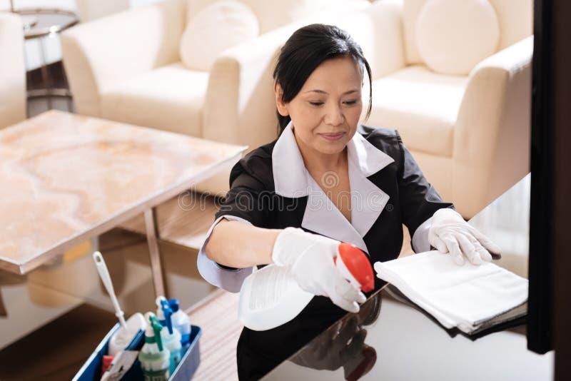 Agente de limpeza agradável agradável da pulverização da mulher na tabela imagens de stock