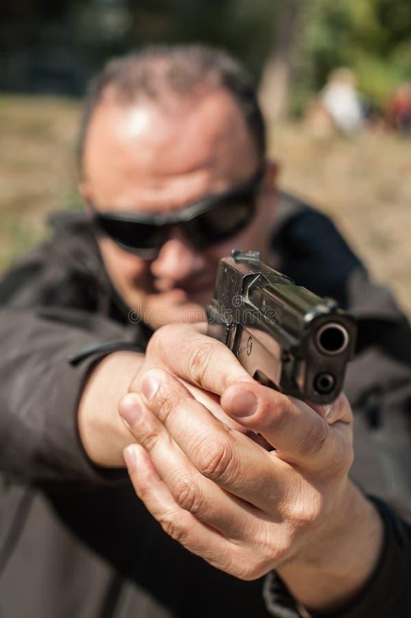 Agente de polícia e escolta que apontam a pistola para proteger do atacante fotos de stock royalty free