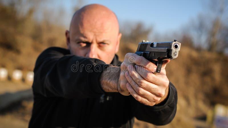 Agente de polícia e escolta que apontam a pistola para proteger do atacante fotos de stock