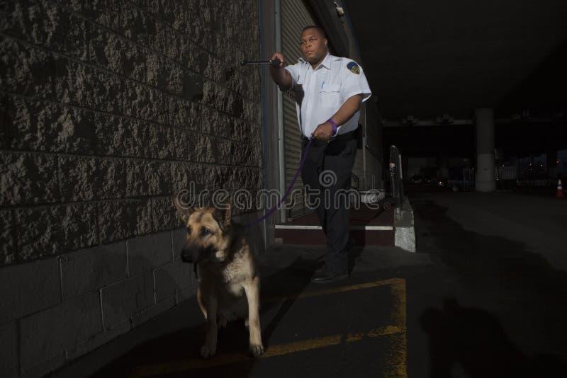 Agente de segurança In Alleyway Pursuit com cão imagem de stock