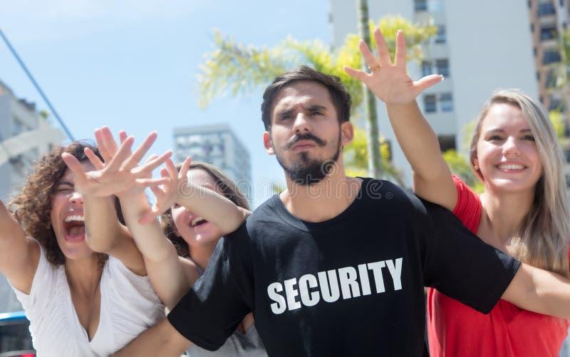 Agente de segurança restrito com os fanáticos no concerto imagens de stock royalty free