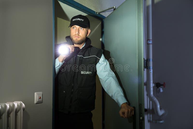 Agente de segurança Searching With Flashlight na sala imagens de stock royalty free