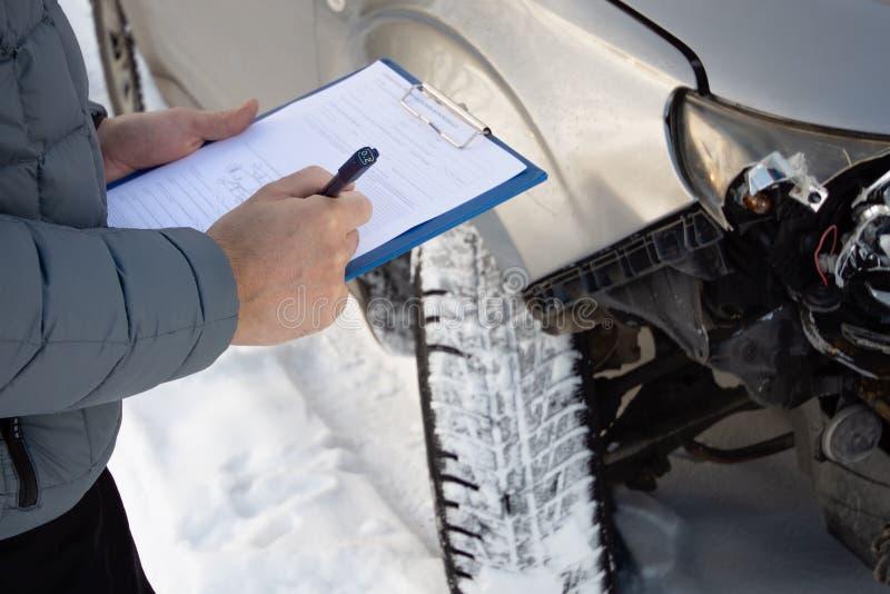 Agente de seguro que comprueba el coche después de accidente de tráfico y que rellena el impreso de los detalles del accidente imagenes de archivo